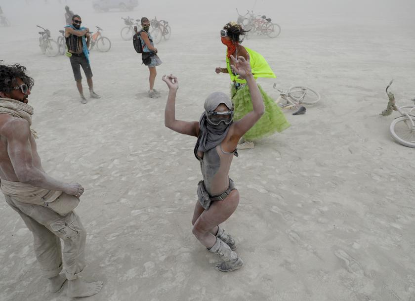 Burning Man participants dance to the music of an art car in the midst of a driving desert dust storm at the Burning Man festival in the Black Rock Desert of Nevada