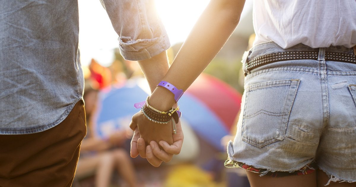 Couple holding hands near tents at music festival